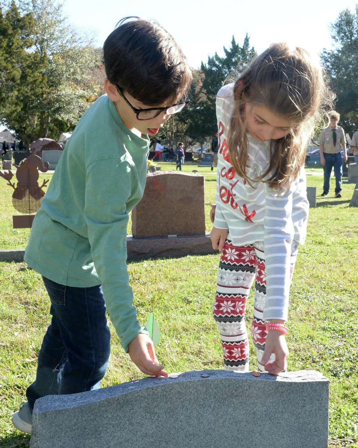 Blake (8) and Avery (10) Torrey place pennies on a grave during the National Wreaths Across America Ceremony at Magnolia Cemetery, Saturday, December 14, 2019 in Katy, TX.