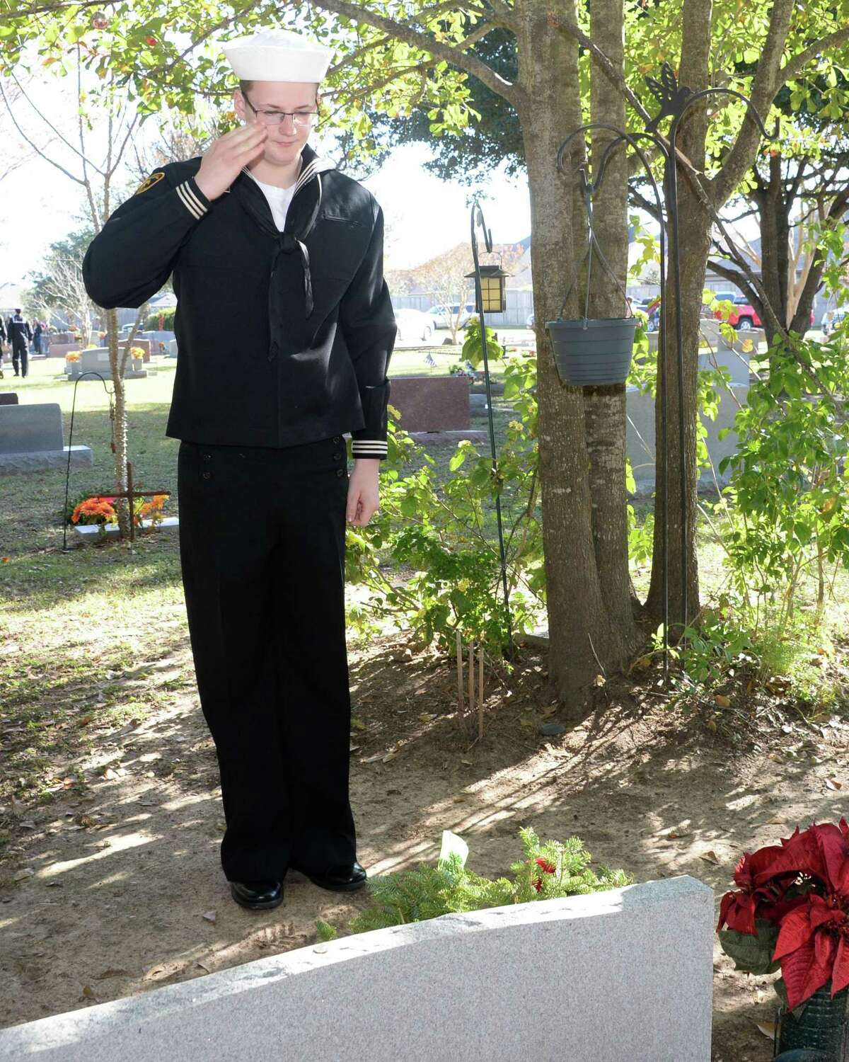 US Navy Sea Cadet Nicholas Geiger salutes after placing a wreath on a grave during the National Wreaths Across America Ceremony at Magnolia Cemetery, Saturday, December 14, 2019 in Katy, TX.