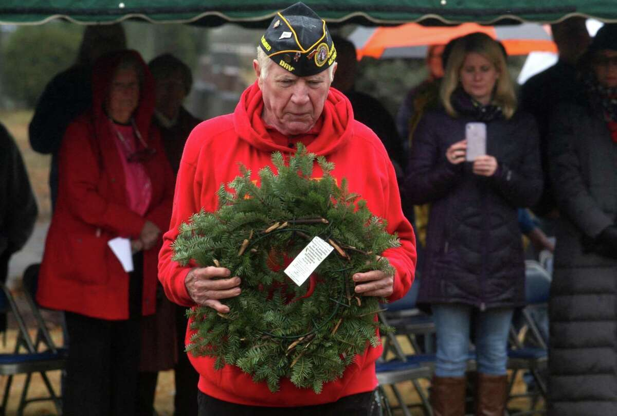 US Marine veteran Adam Lula, with the Disabled American Veterans Chapter 15 in Milford, lays a wreath honoring Marine Corp veterans during the annual Wreaths Across America ceremony held at Kings Kighway Cemetery in Milford on Saturday.
