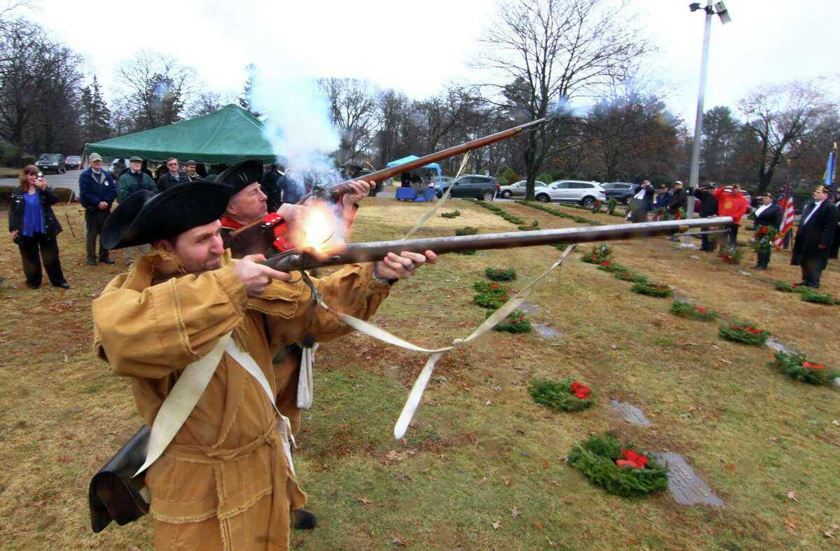 Sons of the American Revolution members Dave Perkins and Chris Bandecchi, in front, perform a musket salute.