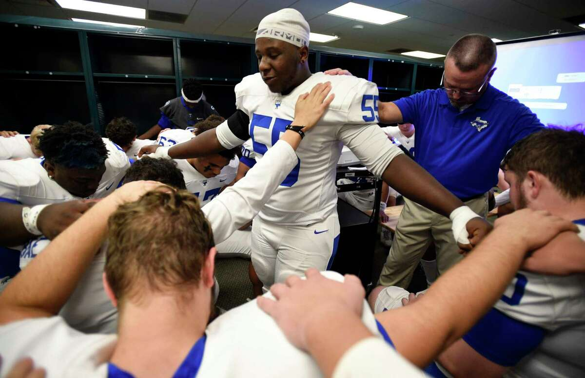 Katy Taylor defensive lineman Ja'Miles Pryor, center, leads a team prayer with head coach Chad Simmons, right, before a 6A division II state semifinal high school football playoff game Austin Westlake, Saturday, Dec. 14, 2019, in Waco, TX.