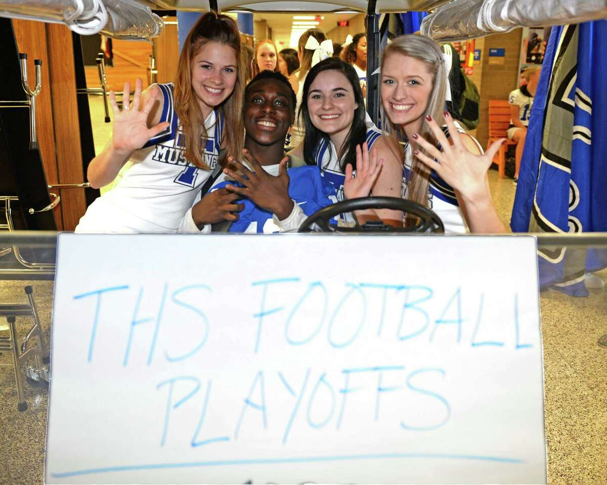 Students display five fingers to signify the fifth playoff round while participating in a send-off ceremony for the Katy Taylor High School varsity football team as they prepare to play Austin Westlake in a State Semifinal playoff game in Waco.