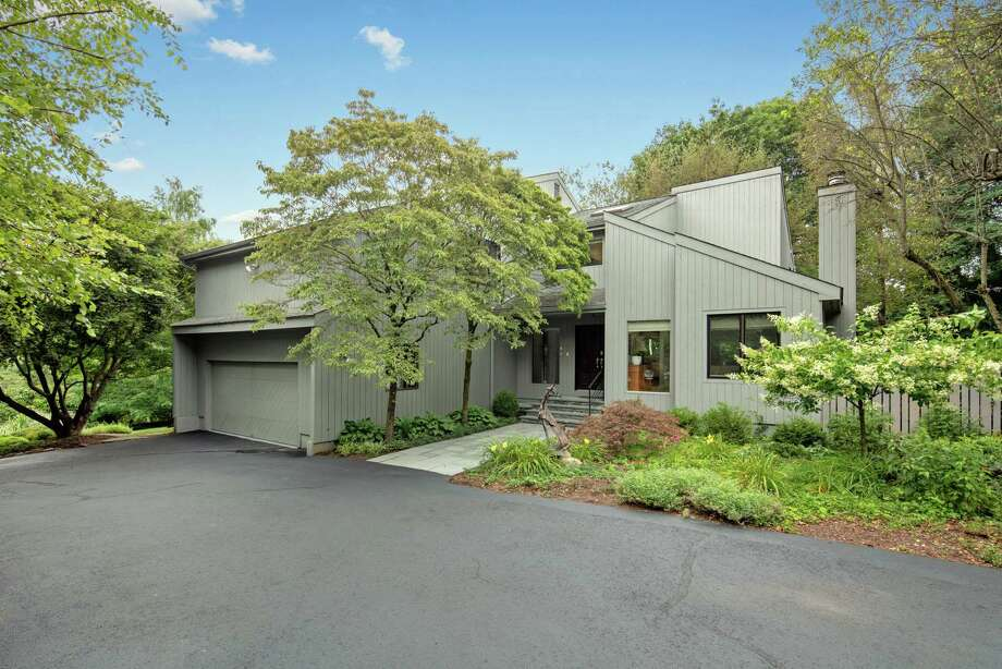 The gray contemporary house at 49 Bayberry Lane features eight rooms and 4,015 square feet of living space.