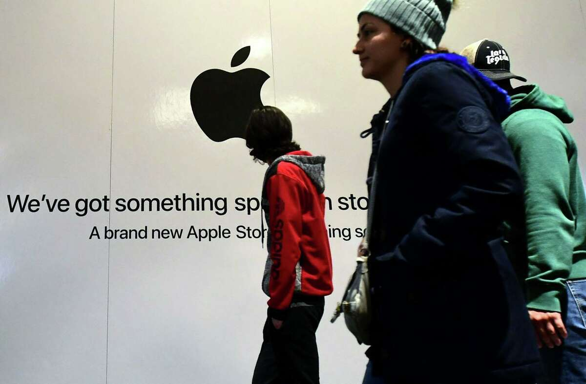 Shoppers walk past the sign heralding the arrival of the Apple store in the new SoNo Collection mall Saturday, December 14, 2019, in Norwalk, Conn.