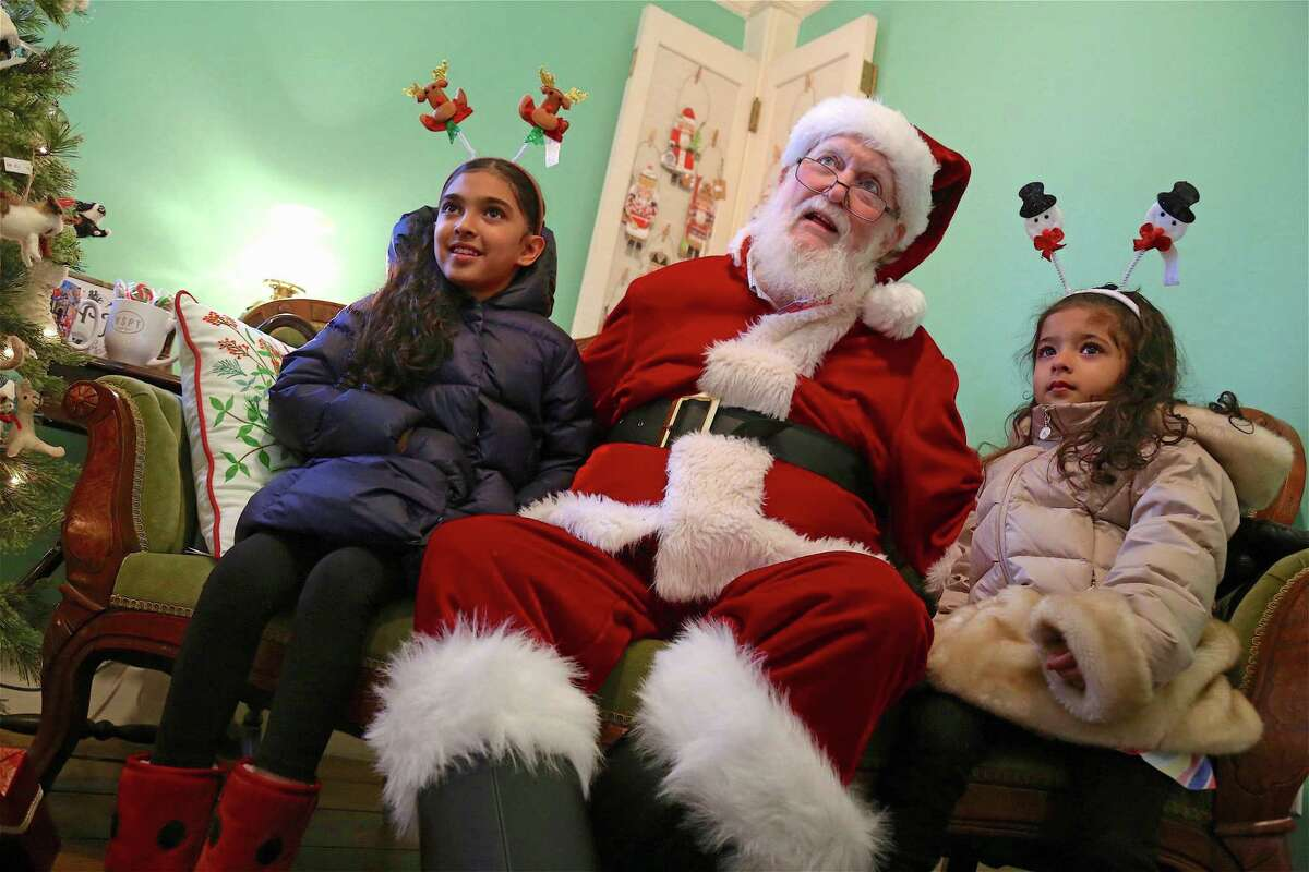 Enjoying a moment with Santa are Yahvi Chopra, 7, of Westport, and her sister Kashish, 3, at the Westport Museum for History and Culture's Jingle Bell Rock event on Dec. 14 in Westport.