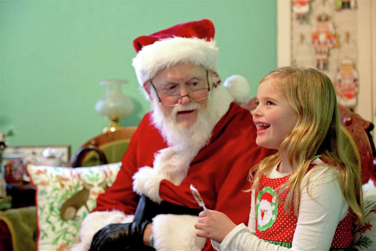 Colette Casey, 6, of Westport, has a smile for Santa at the Westport Museum for History and Culture's Jingle Bell Rock event on Dec. 14 in Westport.