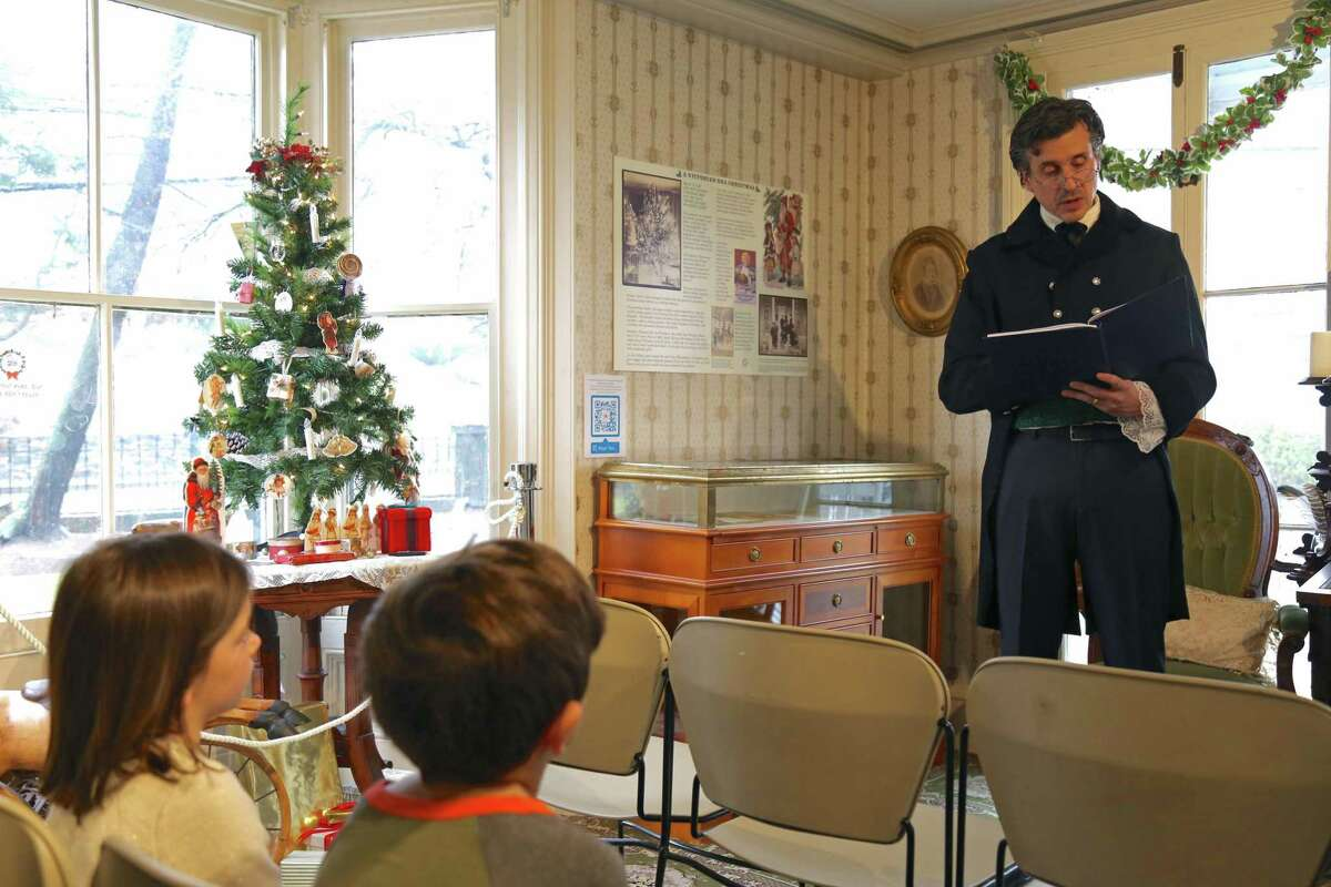 """Board member and actor Greg Porretta of Westport does a reading of """"A Christmas Carol"""" as Charles Dickens at the Westport Museum for History and Culture's Jingle Bell Rock event on Dec. 14 in Westport."""