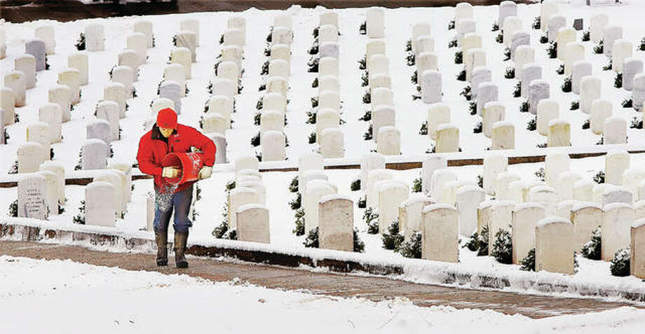A worker was out spreading salt on the walkway he just shoveled Monday morning in the snow covered U.S. National Cemetery on Pearl Street in Alton. Sunday's rash of accidents gave way to digging out Monday morning just before another wave of snow moved into the area, with almost all area schools closed Monday.