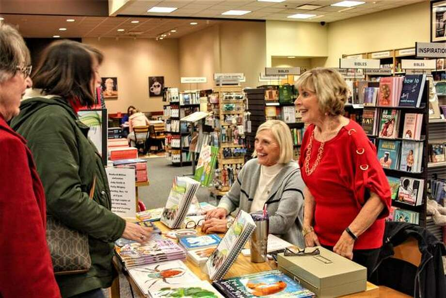 Authors Judy Smith, far right, and Patty Wrigley, second from right, greet a former colleague, left, during the pair's book signing at Books-A-Million on Saturday in Edwardsville. Photo: Andrew Malo|For The Intelligencer