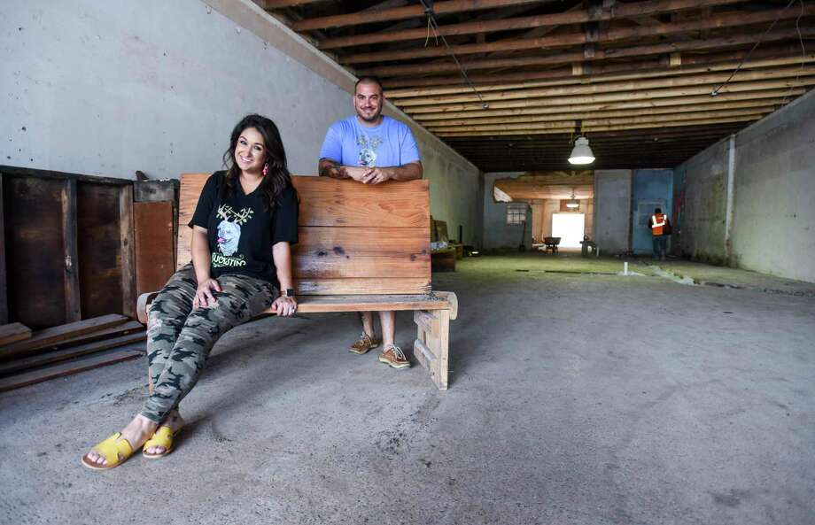 Gabi Blanco and Justin Buchanan-Lopez pose for a photo inside the future site of the Buckstin Brewing in Nederland on Monday. The bench Blanco sits on comes from Esther's Seafood and Oyster bar. Photo taken on Monday, 07/08/19. Ryan Welch/The Enterprise Photo: Ryan Welch, Beuamont Enterprise / The Enterprise / © 2019 Beaumont Enterprise