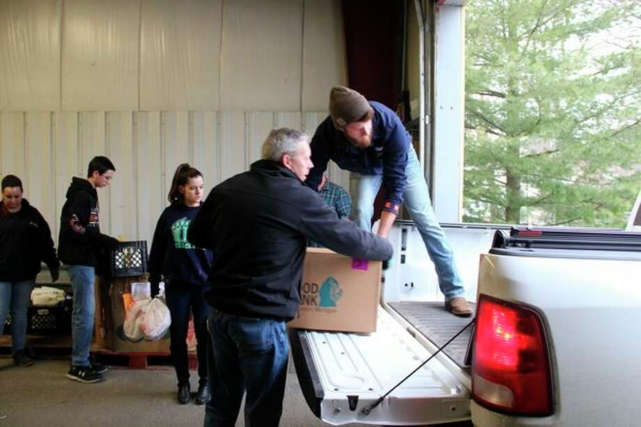 Volunteers help load up trucks for the 2019 Care & Share. About 350 boxes with food and toiletries in total were distributed to Huron County's needy. (Robert Creenan/Huron Daily Tribune)