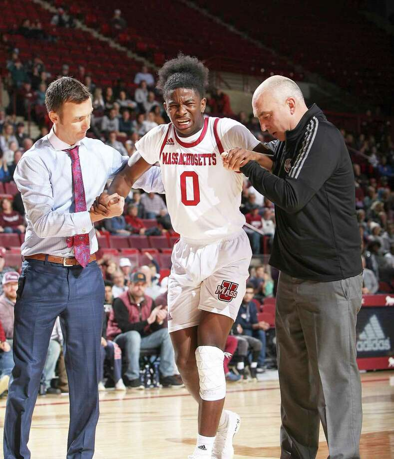 Massachusetts head coach Matt McCall, right, and a team trainer help John Buggs III off the floor after an injury against Central Connecticut State in the second half of an NCAA college basketball game in Amherst, Mass. Photo: J. Anthony Roberts / Associated Press / The Republican
