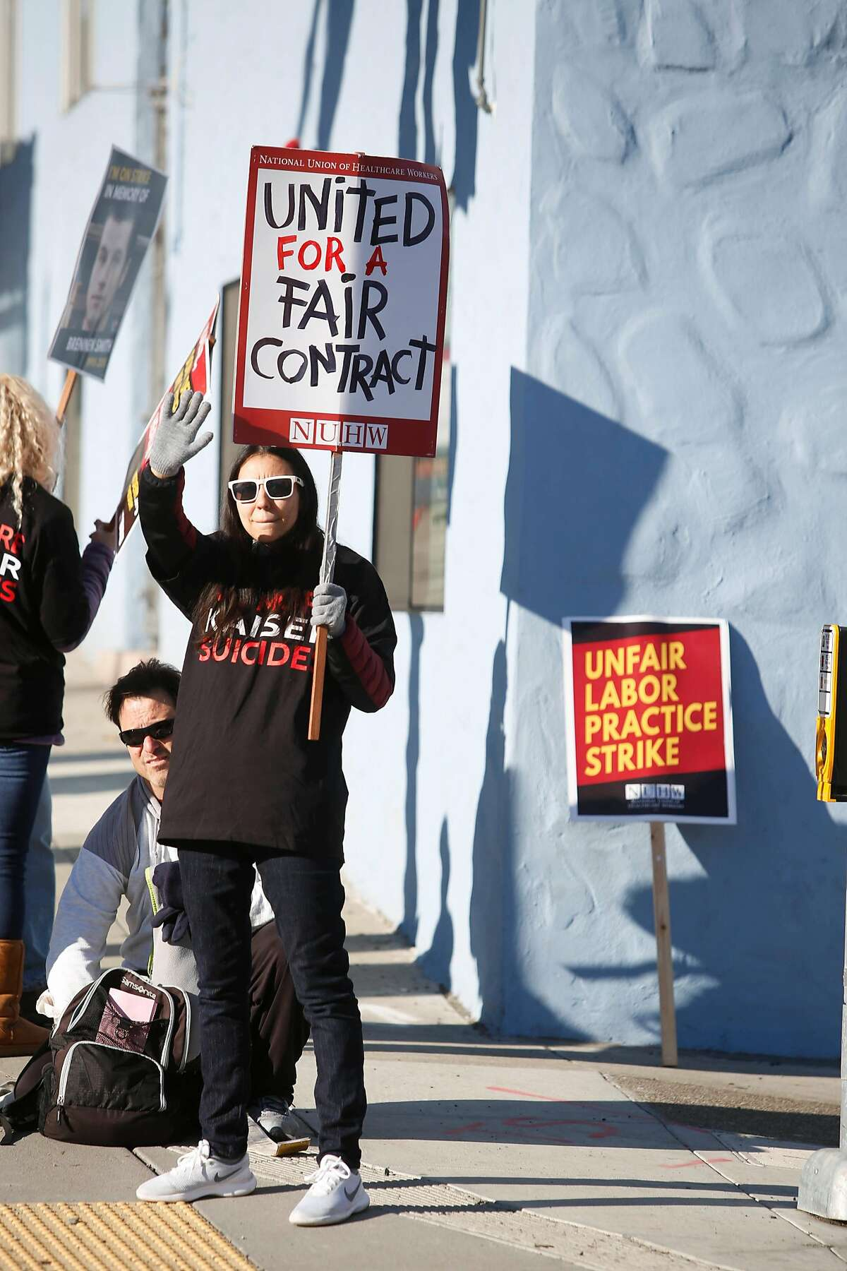 Joanna Mendoza, Kaiser psychologist, waves to passing cars honking support as she stands on Geary Boulevard while picketing with other members of the National Union of Healthcare Workers, outside Kaiser Permanente San Francisco Medical Center on Monday, December 16, 2019 in San Francisco, Calif.