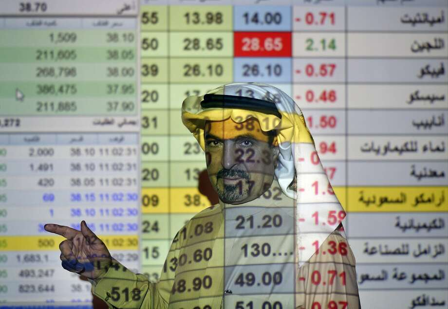 A trader talks to others in front of a screen displaying Saudi stock market values at the Arab National Bank in Riyadh, Saudi Arabia, Thursday, Dec. 12, 2019. Photo: Amr Nabil, Associated Press