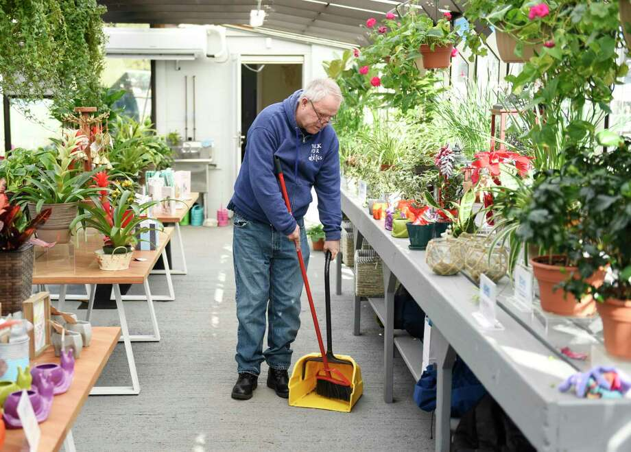 Abilis client Paul Dick cleans up the greenhouse at Abilis Gardens & Gifts in the Glenville section of Greenwich, Conn. Tuesday, Dec. 18, 2018. The shop offers a variety of holiday gifts, including candles and bath products handmade by Abilis clients. Photo: File / Tyler Sizemore / Hearst Connecticut Media / Greenwich Time