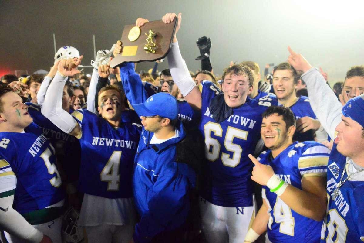 The Newtown football team celebrates its 13-7 win over Darien in the CIAC Class LL football championship on Saturday, December 14, 2019 at Trumbull High School in Trumbull, Conn.