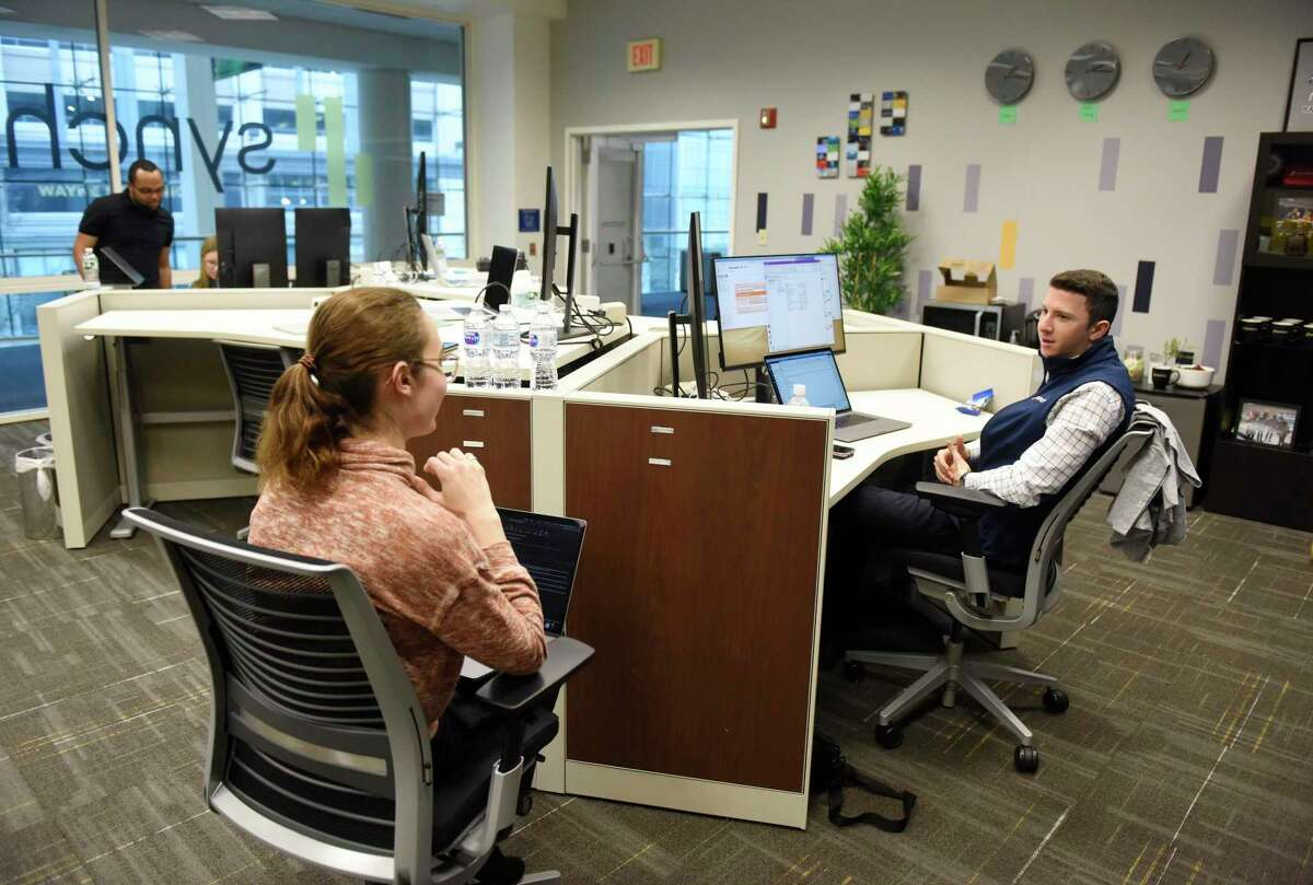 Synchrony employees Brianna Boyce and Marc Senatore work at the new Synchrony Digital Technology Center at the University of Connecticut Stamford branch in Stamford, Conn. Monday, Dec. 16, 2019. Synchrony not only opened a Digital Technology Center at UConn Stamford on Monday, but also announced a donation of $1 million to UConn's new free tuition program.
