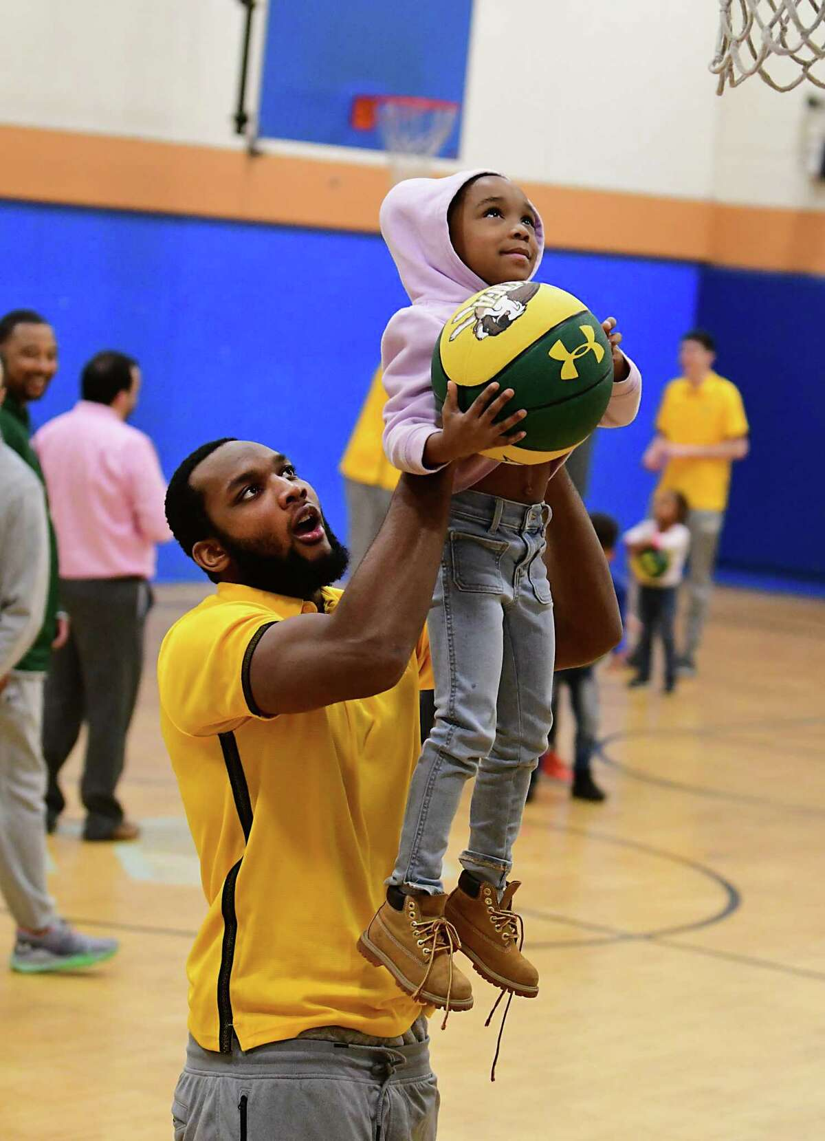 Siena basketball player Sammy Friday helps La'val Brown, 5, reach the basket at the Boys & Girls Clubs of the Capital Area?•s Troy Clubhouse on Monday, Dec. 16, 2019 in Troy, N.Y. Players and coaches from the Siena men?•s basketball team hosted a clinic for local young athletes. (Lori Van Buren/Times Union)