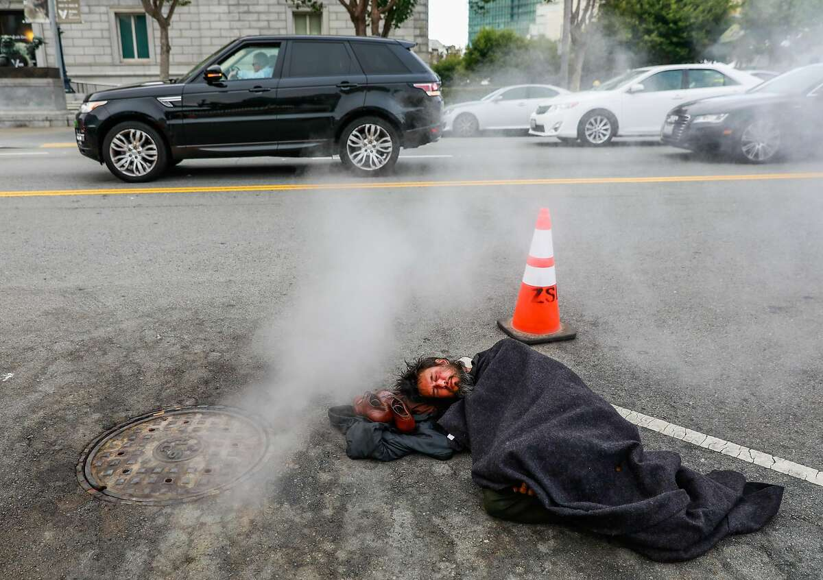 Homeless man Kevin Christopher Highfield, 39, tries to rest in a parking spot on Larkin Street as cars pass by him in San Francisco, California, on Tuesday, June 18, 2019. Kevin said he has been homeless since he was 18 years old after getting kicked out of the house by his mother. He broke his left leg and it never properly healed so it causes him great pain. Photo taken on Larkin Street between McAllister and Fulton Streets at 6:46pm