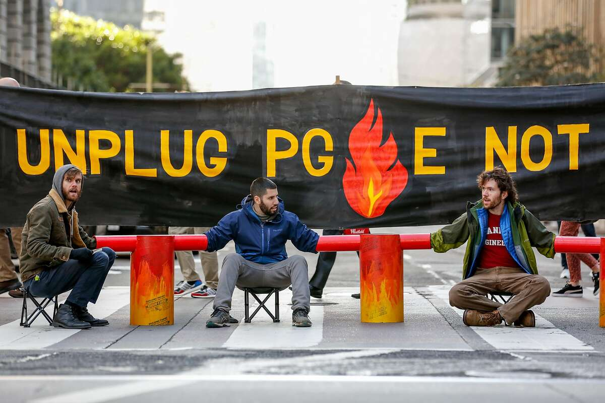 Protesters Benny Zank (C), Wyatt Smith (R) and other protesters DSA and other organizations block Beale Street in front of PG&E headquarters by chaining themselves together on Monday, December 16, 2019 in San Francisco, Calif.