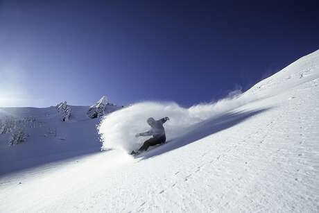 A snowboarder shreds on a virgin slope on a bluebird day out of Alpine Meadows at Lake Tahoe