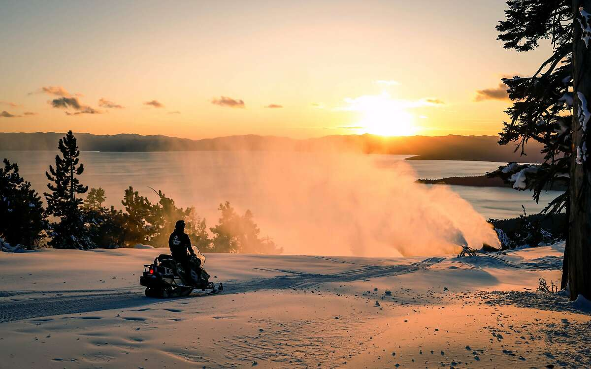 A ski patrol officer on a snowmobile watches a snowmaking operation at Crystal Express at Diamond Peak Ski Area