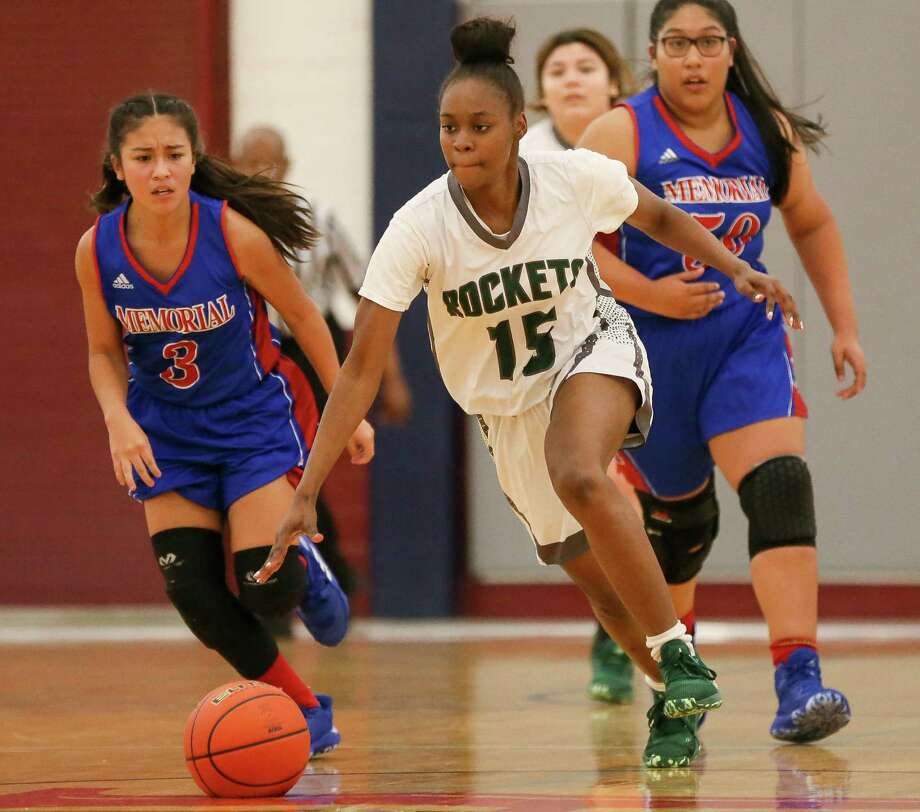 Kennedy's Deshawn Vallerie drives the ball past Memorial's Skylar Herrera, left, and Avigail Sifuentes, right, in their District 26-5A girls basketball game with Memorial at Edgewood Gym on Dec. 10, 2019. Photo: Marvin Pfeiffer /Staff Photographer / **MANDATORY CREDIT FOR PHOTOG AND SAN ANTONIO EXPRESS-NEWS/NO SALES/MAGS OUT/TV