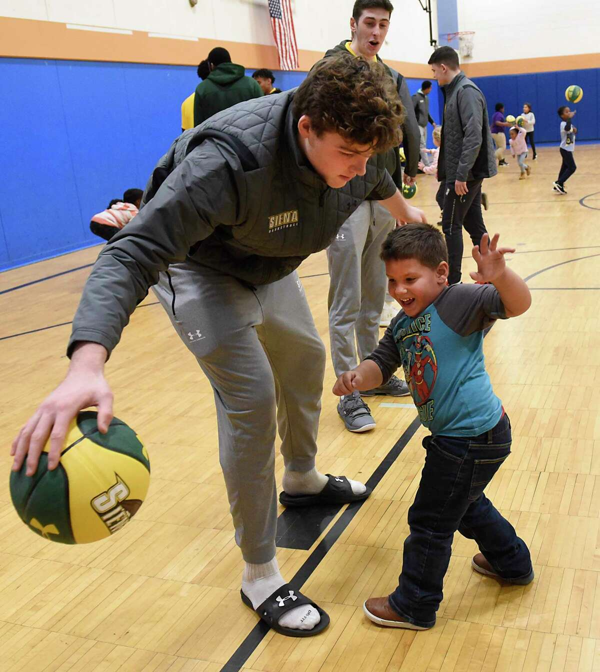 Isaiah Colon, right, gets some dribbling tips from Siena basketball player Kyle Young at the Boys & Girls Clubs of the Capital AreaA?•s Troy Clubhouse on Monday, Dec. 16, 2019 in Troy, N.Y. Players and coaches from the Siena menA?•s basketball team hosted a clinic for local young athletes. (Lori Van Buren/Times Union)