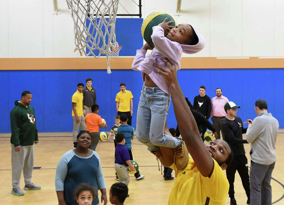 Siena basketball player Sammy Friday helps La'val Brown, 5, reach the basket at the Boys & Girls Clubs of the Capital AreaA?•s Troy Clubhouse on Monday, Dec. 16, 2019 in Troy, N.Y. Players and coaches from the Siena menA?•s basketball team hosted a clinic for local young athletes. (Lori Van Buren/Times Union)