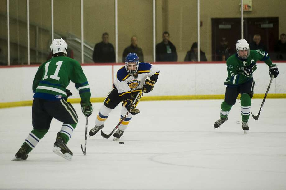 Midland High's Matthew Babinski (center), shown in a game against Saginaw Heritage in February 2018, has rejoined the Chemics after playing junior hockey for more than a year. Photo: Daily News File Photo