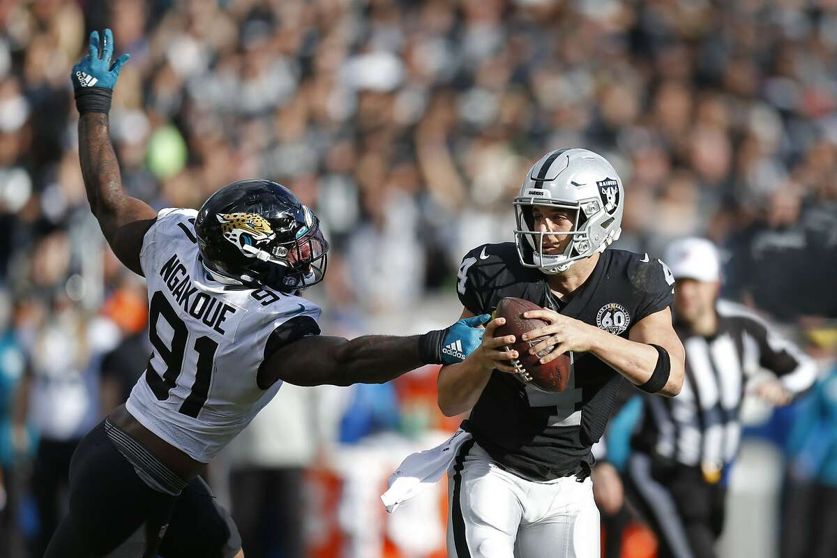 Oakland Raiders quarterback Derek Carr tries to get away from Jacksonville Jaguars defensive end Yannick Ngakoue (91) during the second half of an NFL football game in Oakland, Calif., Sunday, Dec. 15, 2019. (AP Photo/D. Ross Cameron)