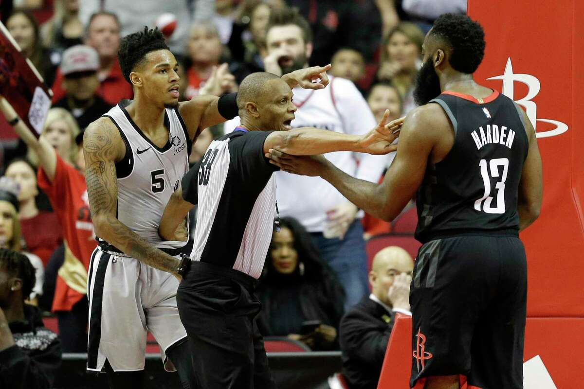 Referee Michael Smith, center, separates San Antonio Spurs guard Dejounte Murray (5) and Houston Rockets guard James Harden during the first half of an NBA game Monday, Dec. 16, 2019, in Houston.