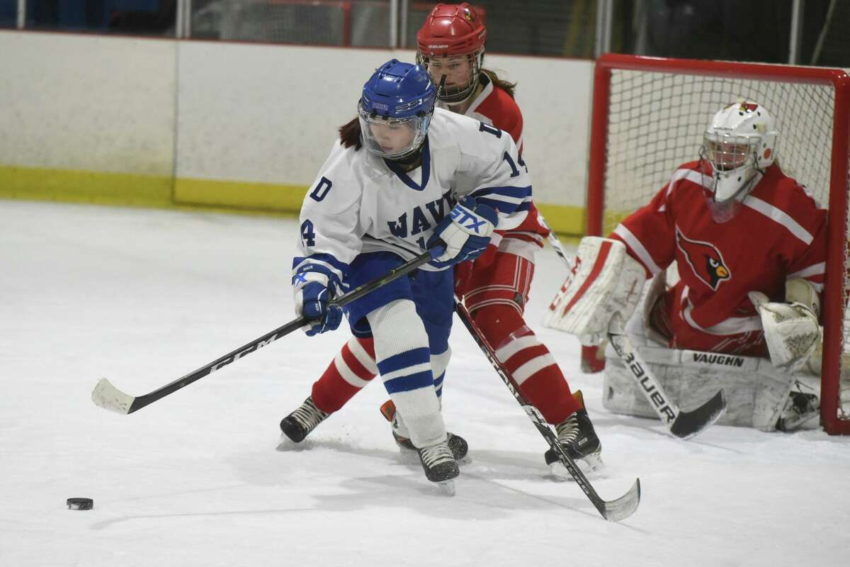 Darien's Caitlin Chan (14) gets to the puck in front of the Greenwich goal during the state quarterfinals at the Darien Ice House on March 2.