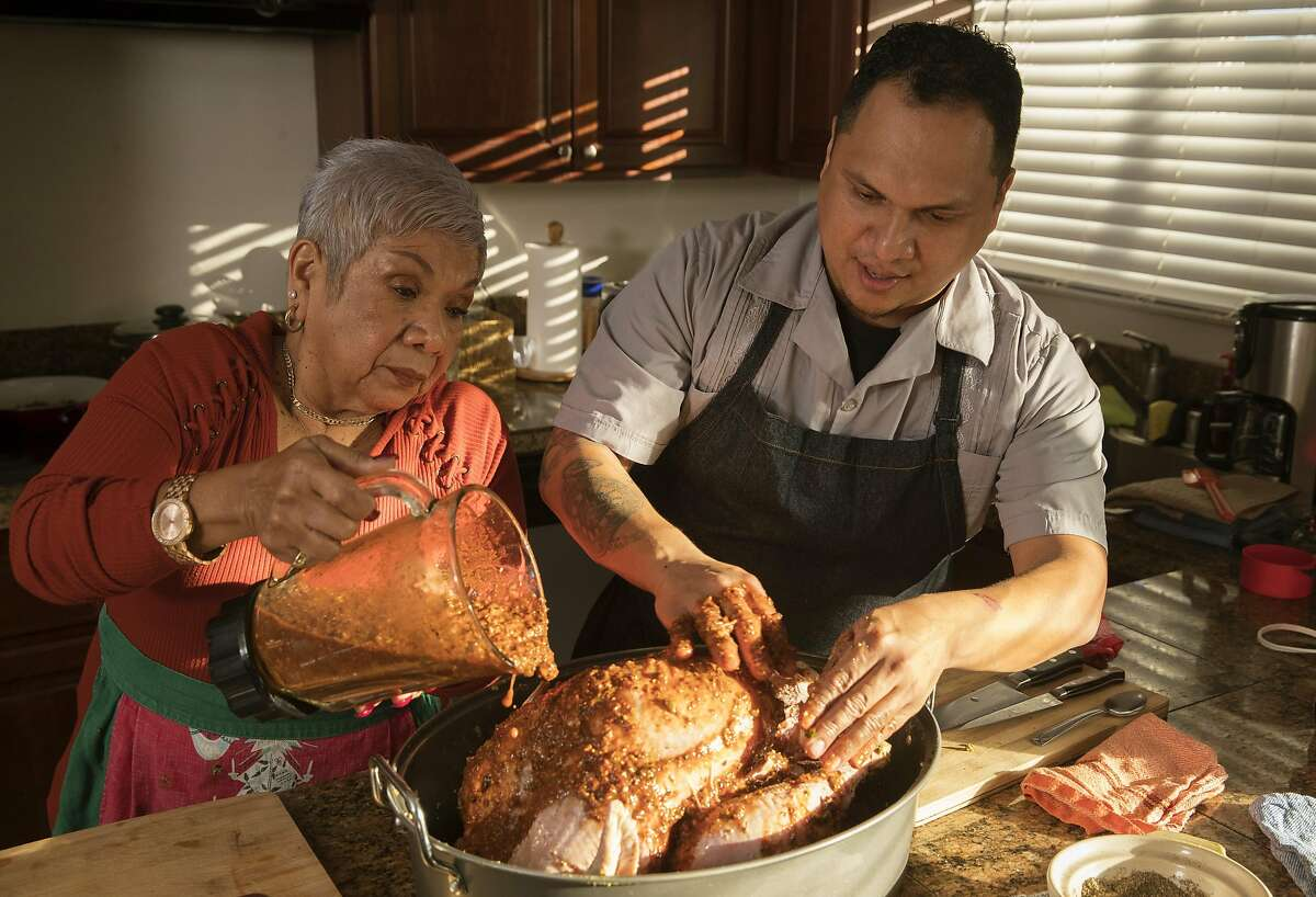 Jonnatan Leiva and his mom Anna Leiva prepare a family recipe of drunken turkey, or Pavo Borracho, in his sister's home in Vacaville, Calif., on Monday, December 9, 2019. The dish is a tradition started by his great grandmother in El Salvador that they've continued after immigrating to the United States.