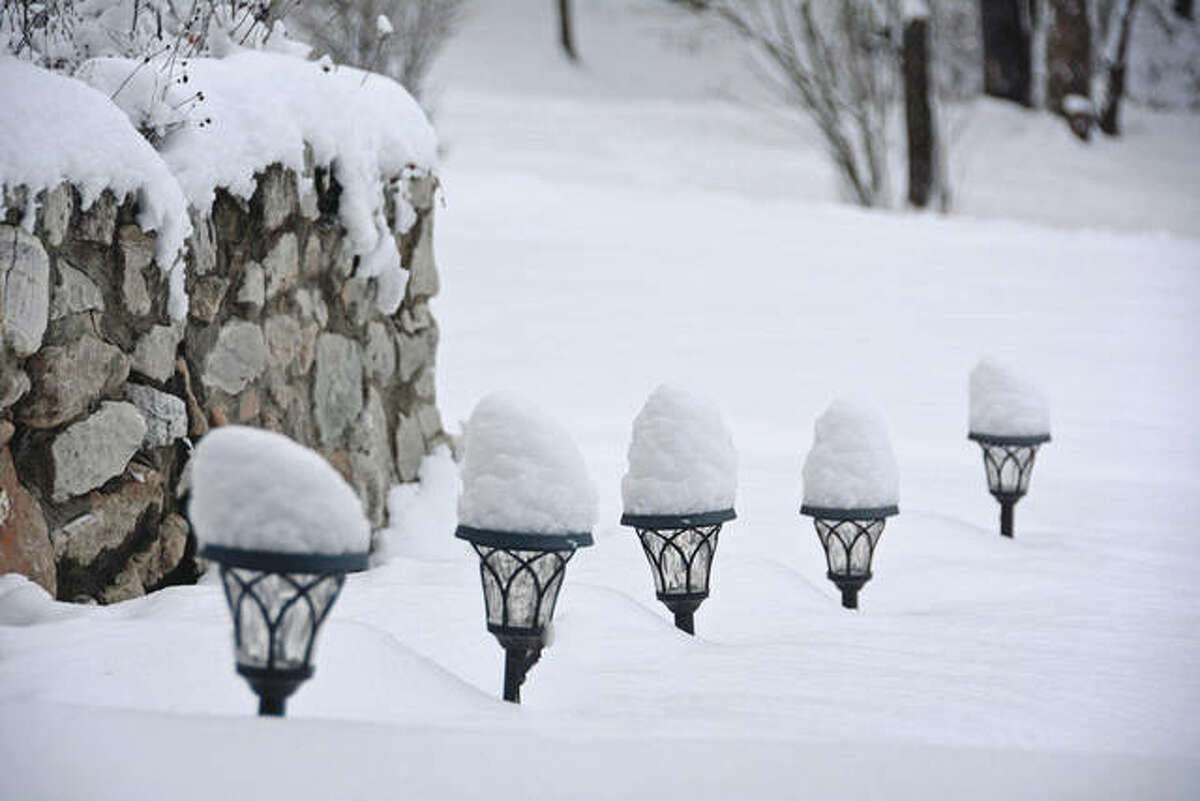 Snow atop a row of solar lights gives them the appearance of ice cream cones.