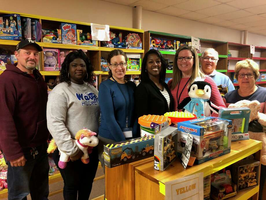 TEAM, Inc. Director of Early Childhood Jamie Peterson, fifth from left, and TEAM Development and Community Manager Lisa Savoie, fourth from left, with volunteers at the organization's Toys 4 Kids toy store. Photo: Brian Gioiele / Hearst Connecticut Media / Connecticut Post
