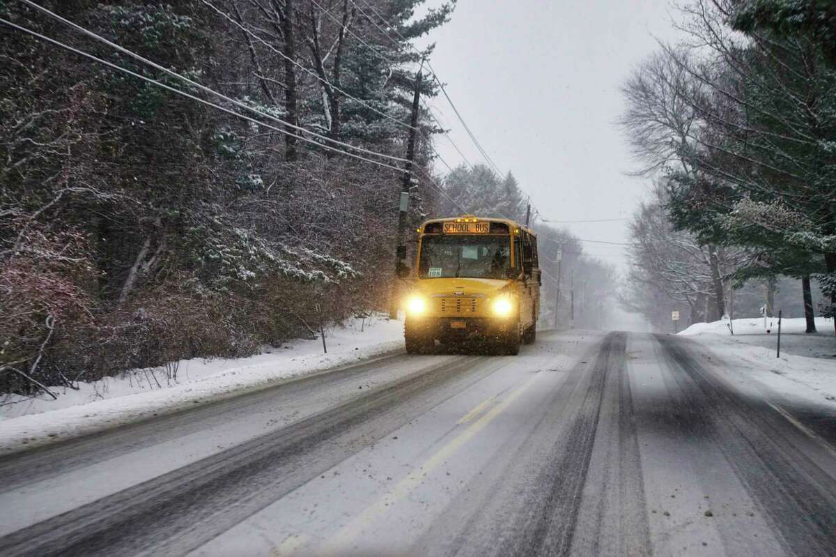 A school bus is driven along a snow covered road on Tuesday, Dec. 17, 2019, in Loudonville, N.Y. Some school districts were delayed or canceled while others remained open. (Paul Buckowski/Times Union)