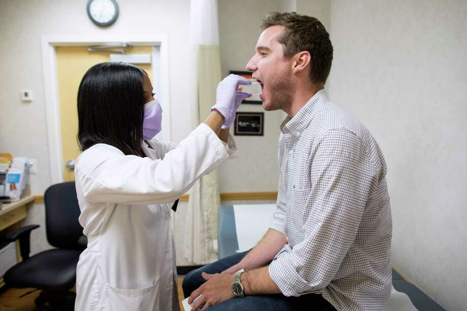 Mike Gaffney, complaining of a sore throat, is examined by Jessica Chung, a nurse practitioner, at a MinuteClinic in a CVS. Photo: BRIAN HARKIN, STR / NYT / NYTNS