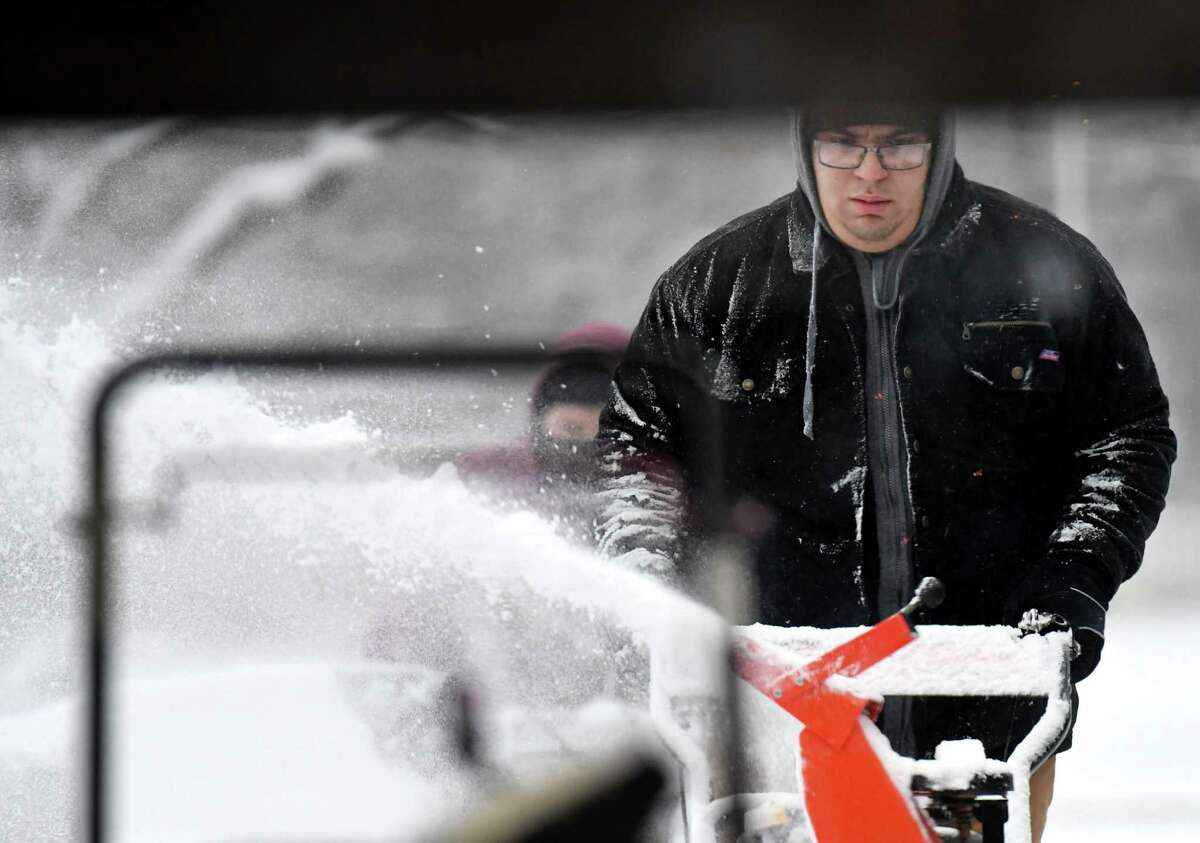 Anthony Moak, left, and Dio Lezama, right, clear snow from the entryway at the Schodack Central School District offices on Tuesday, Dec. 17, 2019, in Schodack, N.Y. (Will Waldron/Times Union)
