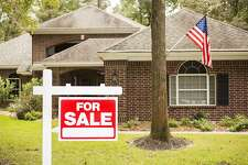 """Red and white """"Home for Sale"""" sign in front of a red brick house that is for sale. Green grass and bushes indicate the spring or summer season. USA flag. Front porch and windows in background. Real estate sign in residential neighborhood. Moving house, relocation concepts."""