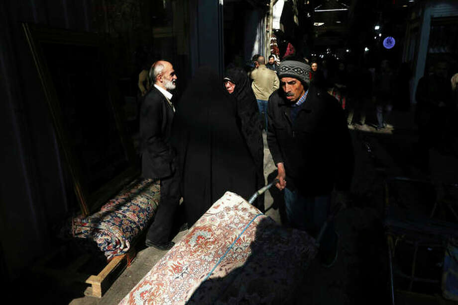 A man carries a rug at the Grand Bazaar in Tehran, Iran, Thursday, Dec. 12, 2019. A new budget designed to resist crippling U.S. trade embargoes was presented to the Iranian parliament on Sunday, as the country aims to depend less on oil revenue next year. (AP Photo/Vahid Salemi)