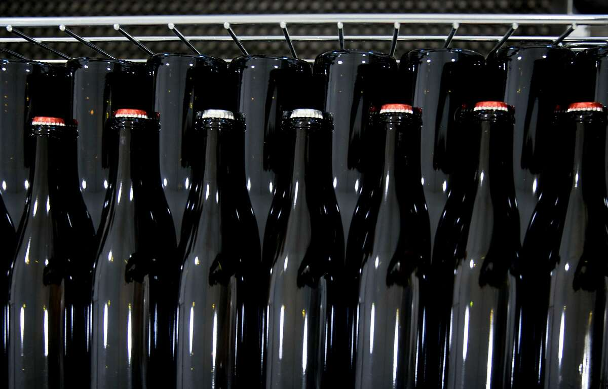Bottles of sparkling wine wait to be labeled as they sit at the Carboniste barrel space inside RD Winery in Napa, Calif. Saturday, Dec. 14, 2019.