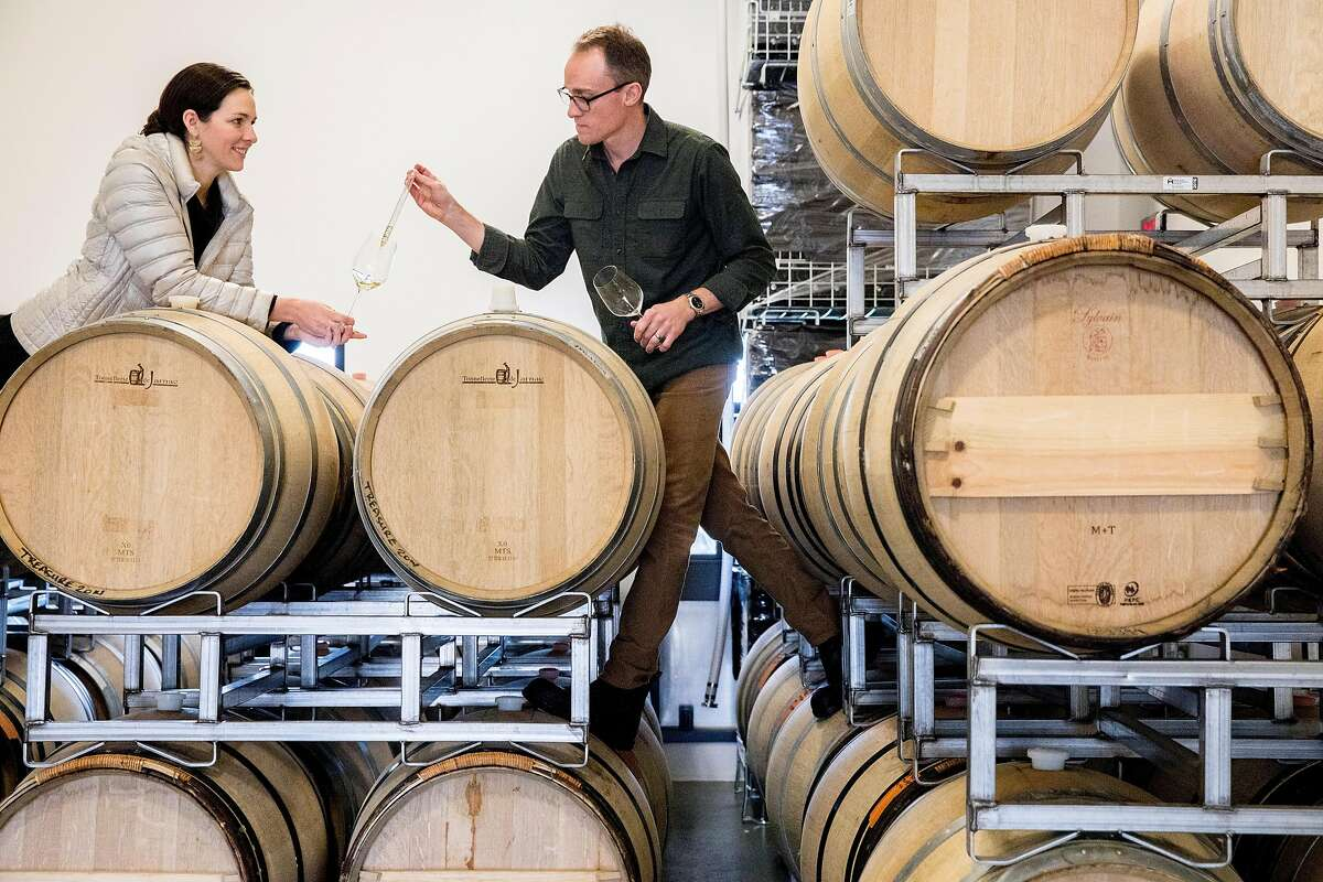 Carboniste owners Jacqueline and Dan Person stand atop barrels while tasting their sparkling wine inside their barrel space at RD Winery in Napa, Calif. Saturday, Dec. 14, 2019.