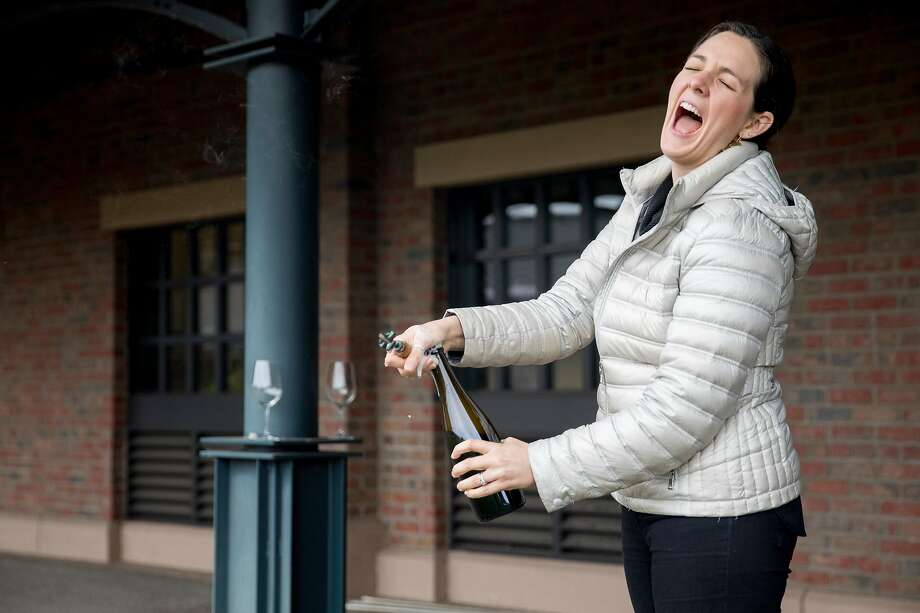 Jacqueline Person disgorges a bottle of sparkling wine outside RD Winery in Napa. Photo: Jessica Christian / The Chronicle