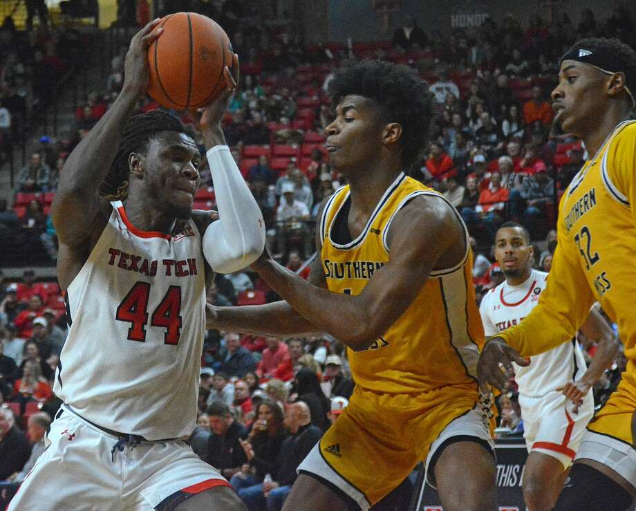 Texas Tech's Chris Clarke drives into the lane against Southern Miss defenders Tyler Stevenson and Leonard Harper-Baker (32) during their NCAA men's basketball game on Monday in the United Supermarkets Arena in Lubbock. Photo: Nathan Giese/Planview Herald