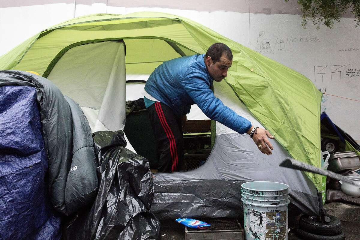 Orion Diaz throws things away from inside his tent while gathering his belongings during a sweep of homeless tents and encampments by the Department of Public Works and San Francisco Police along Willow Street in San Francisco, Calif. Wednesday, Dec. 4, 2019.