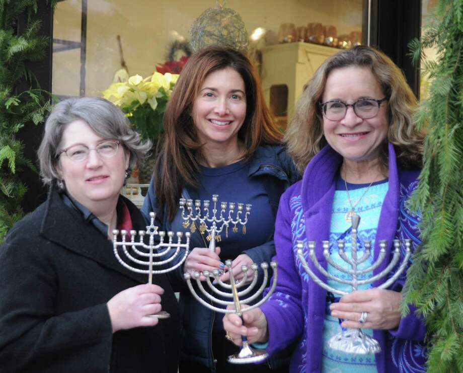 Menorahs have been distributed by Deborah Katchko-Gray, cantor of Congregation Shir Shalom, to village businesses for window display during the holiday season. From left are: Mary Jones of Rodier Flowers, the president of the Downtown Ridgefield merchants association; Shir Shalom member Kimberly Knispel, and Cantor Katchko-Gray. About 35 menorahs have been distributed to business in town the last few years. Upcoming Hanukah events at Shir Shalon include: A celebration at the early childhood center at 11 a.m. on Dec. 20; a Tot Shabbat Dec. 20 at 5:30 p.m.; and a Kabbalat Shabbat for all ages on Dec. 27 at 7:30 p.m. with food and songs. p.m. Photo: Macklin Reid / Contributed Photo