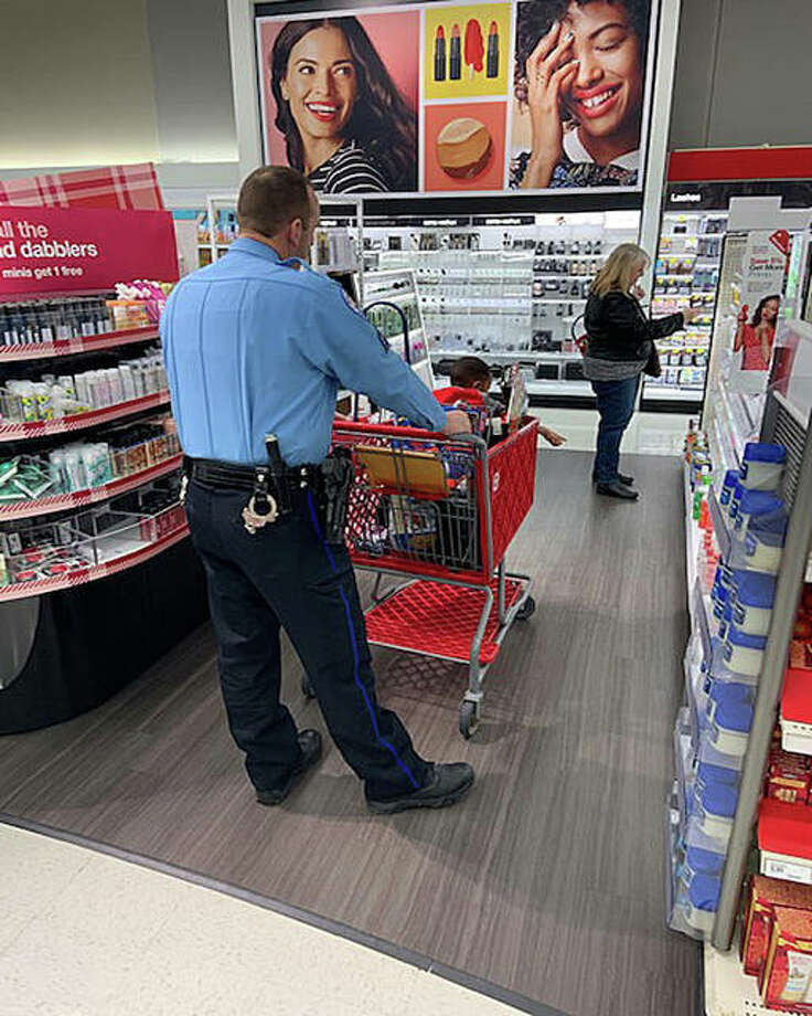 """An Edwardsville Police officer pushes a cart while a child points to an item in the health and beauty section at Target Saturday. This is the 10th year for the city's """"Christmas with a Cop"""" event.   Photo: Courtesy Of The Edwardsville Police Department"""