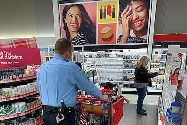 """An Edwardsville Police officer pushes a cart while a child points to an item in the health and beauty section at Target Saturday. This is the 10th year for the city's """"Christmas with a Cop"""" event."""