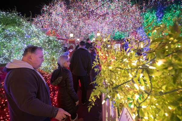 Visitors walk through the Deacon Dave light display. For the past 37 years Deacon Dave has invited everyone to view his Christmas lights display in the front yard of his home in Livermore. It has grown to include over 640,000 lights, the most of any home display in the Bay Area